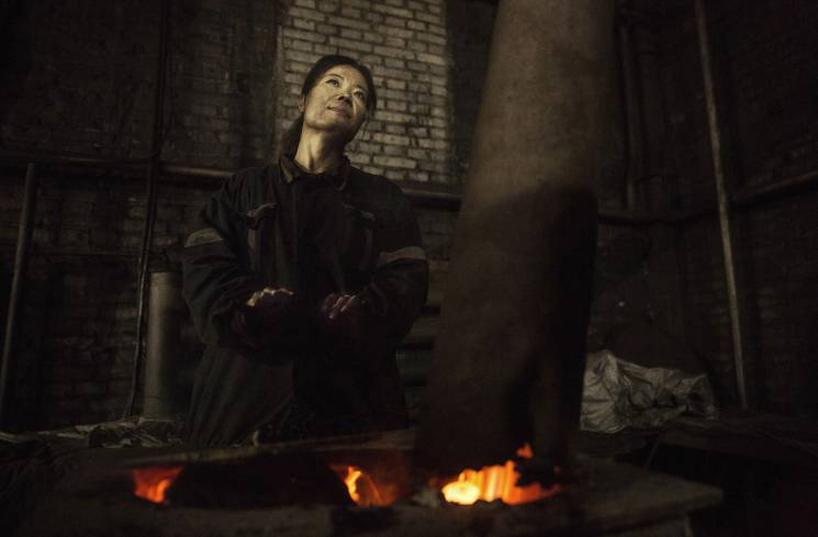 A Chinese mine worker warms herself over a coal stove coal as she takes a break at a mine on November 25, 2015 in Shanxi, China. A history of heavy dependence on burning coal for energy has made China the source of nearly a third of the world's total carbon dioxide (CO2) emissions, the toxic pollutants widely cited by scientists and environmentalists as the primary cause of global warming.; Getty