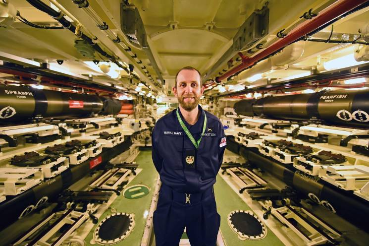 sailor stands in weapons room