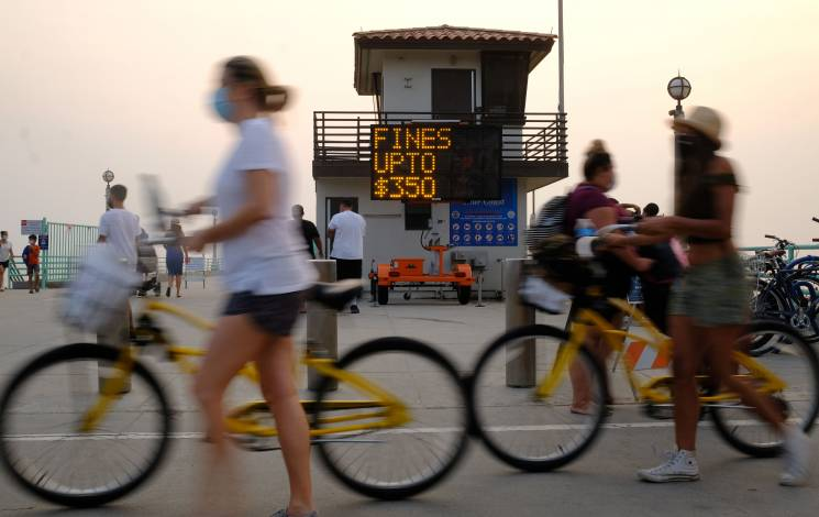 A sign reminding people the fine for not wearing a mask can be as much as $350 is seen by the pier during a heat wave on September 7, 2020 in Manhattan Beach, California, amid the coronavirus pandemic.; Getty