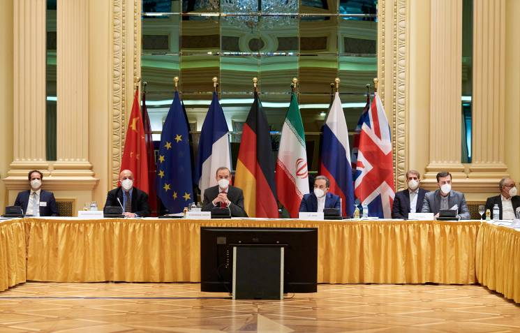 world leaders sit in front of flags