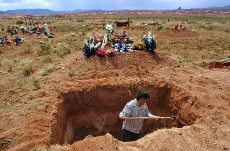 man digs a grave