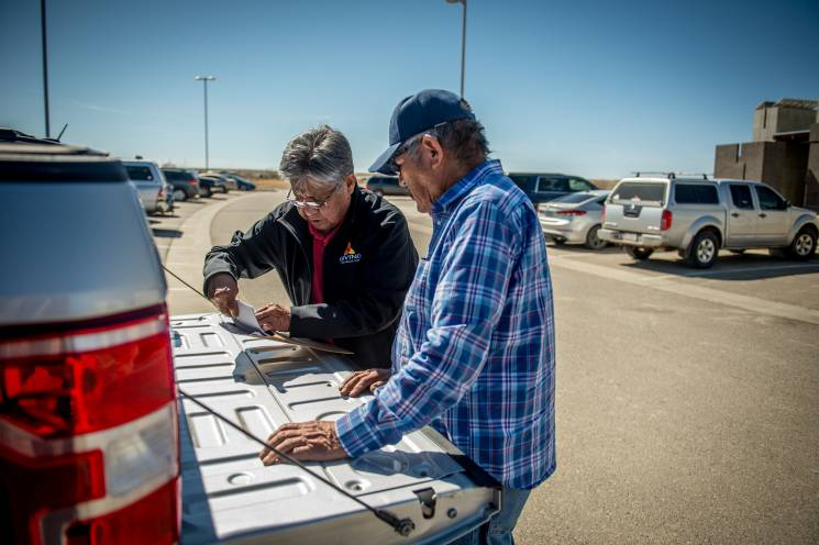 two men sign papers on the tailgate of a pickup truck