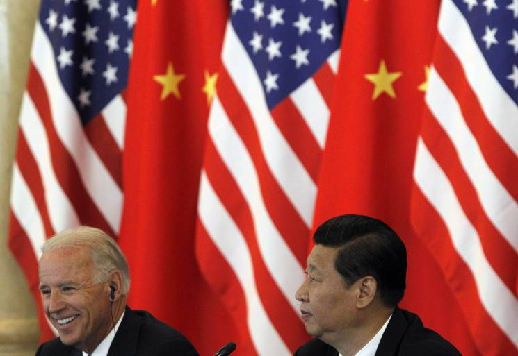 Biden and Xi Jinping sit in front of American and Chinese flags