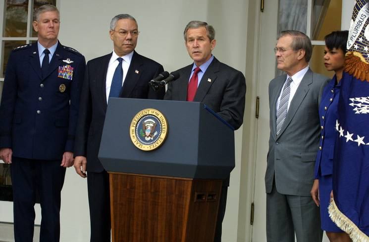 President George W Bush stands at a podium flanked by cabinet members