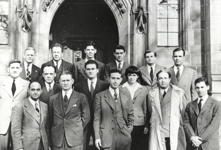 Fourteen men and one woman in pinstripe suits, ties, and serious faces stand in front of a gothic-revival lancet arch at the University of Chicago.