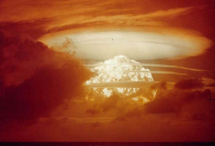 A gigantic mushroom cloud lights the sky a bloody orange.