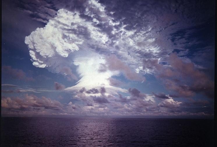 An explosion and mushroom cloud light up a dark purple sky, over a calm ocean.