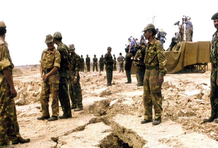 Soldiers stand on either side of a jagged fissure running through the desert floor.
