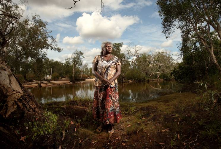 A woman in a patterned shirt and skirt stands in a clearing near a river.