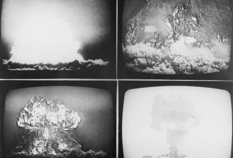 Four televisions screens are shown in a grid, with four different mushroom clouds visible.