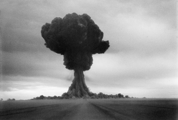 A large black mushroom cloud is visible against a light-grey clouded sky.