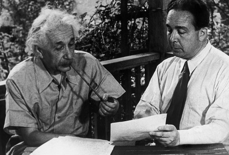 Albert Einstein discusses the contents of a letter with a man in a white shirt and a tie.