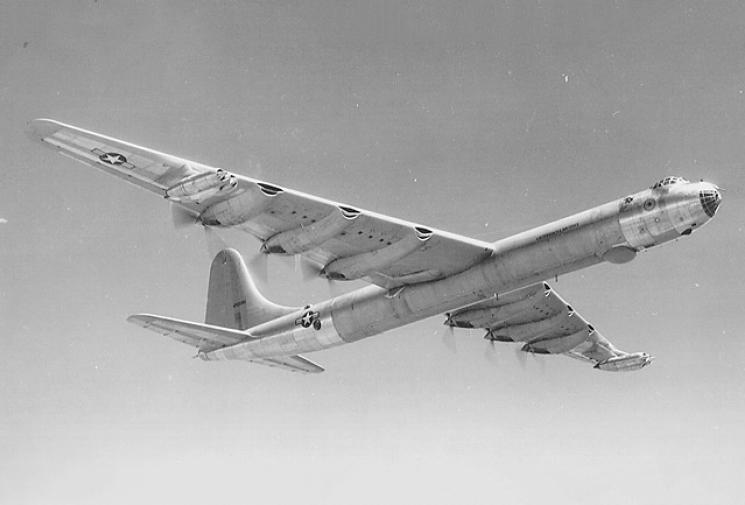 A B-36 in flight, viewed from below against a grey sky.