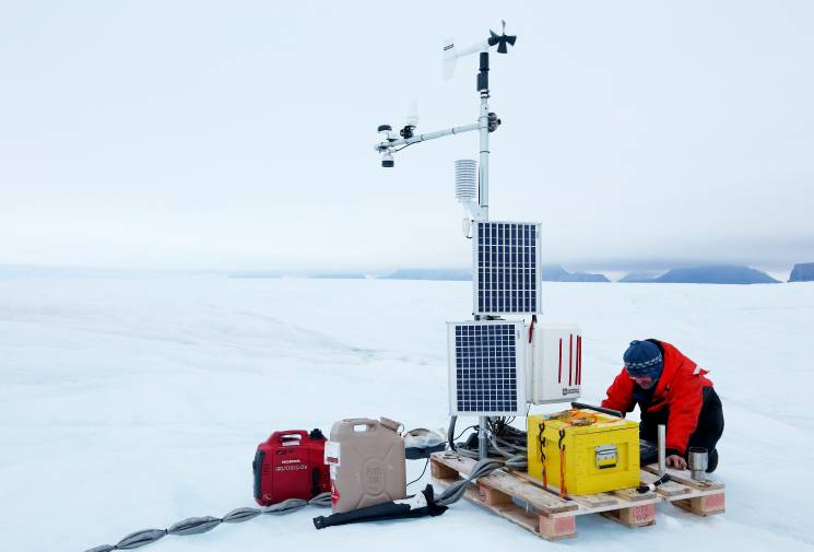 Scientist works with a portable weather station in the Arctic