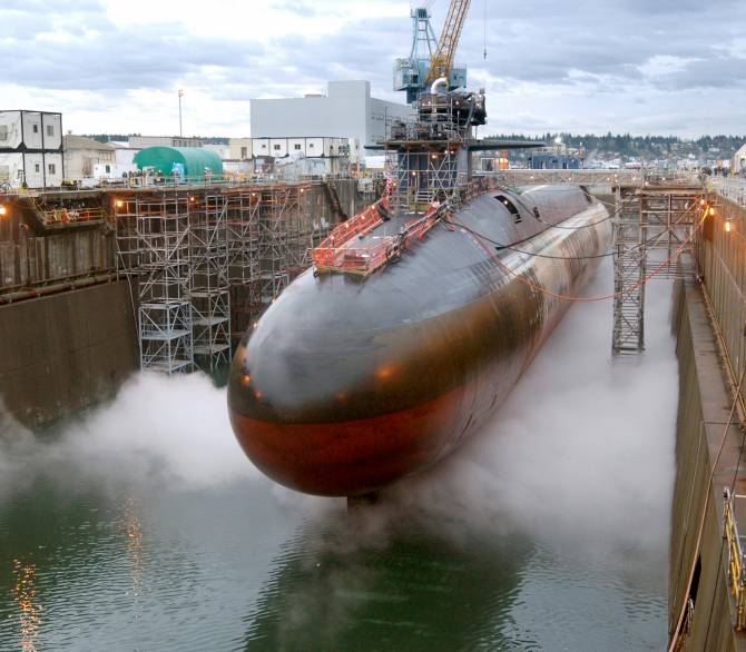 A huge red and black submarine sits in a dock.