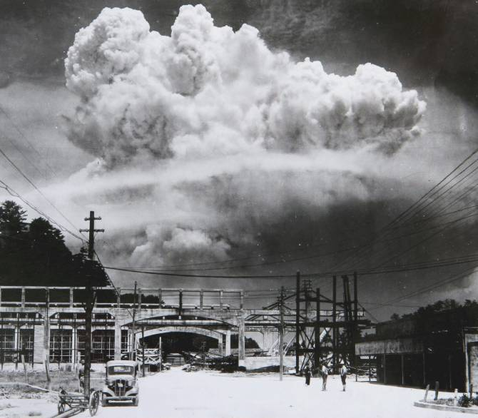 A huge mushroom cloud is seen beyond a desolate looking road.