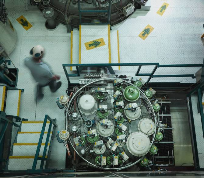 A man in a hard hat walks through a nuclear reactor plant floor.