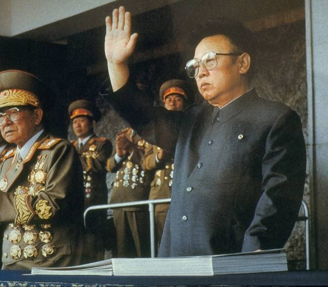 An older Kim Jong Il stands in front of older crowd of military men covered in large medals. Kim Jong Il looks passive, and raises his right hand.