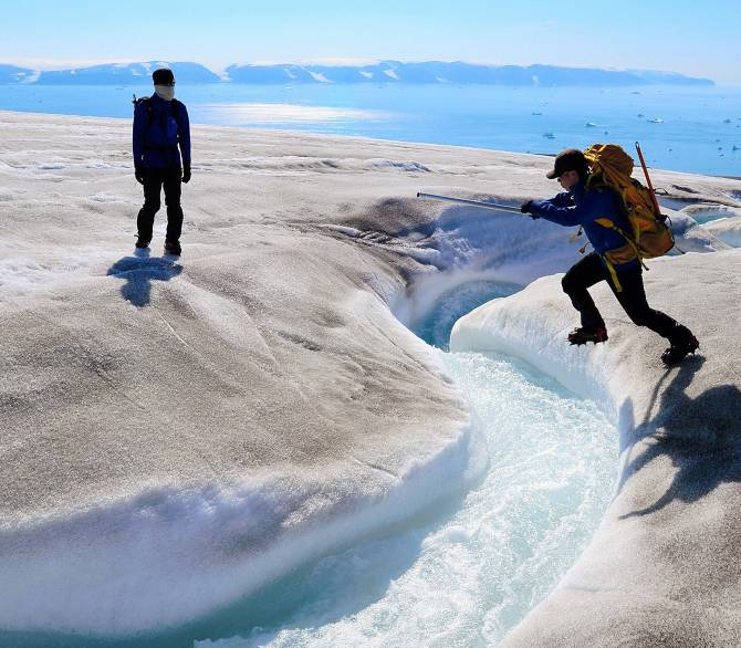 Scientists cross a river on a glacier