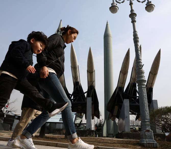 woman and child walk by missile display