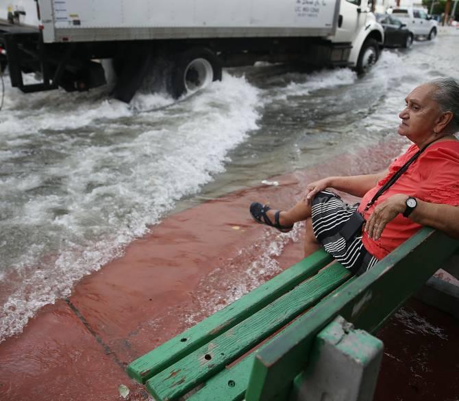 Mayabel Rents espera un autobús junto a una calle inundada, causada por la combinación de la órbita lunar, que causó las mareas altas estacionales, y lo que muchos creen es el aumento del nivel del mar debido al cambio climático, el 29 de septiembre de 2015 en Miami Playa, Florida. La ciudad de Miami Beach se encuentra en medio de un programa de instalación de bombas de aguas pluviales, que costará $ 400 millones y que tomará cinco años. Los funcionarios esperan que éste y otros proyectos eviten que las agu