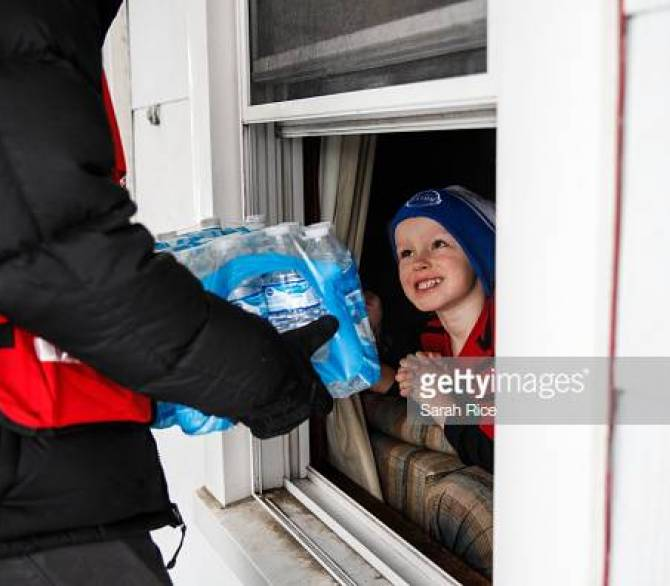Young boy receives a shipment of bottle water at his home; Getty Images