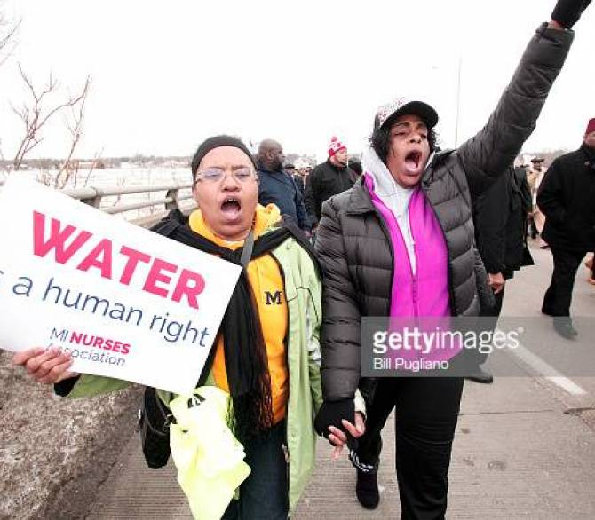 Flint residents carry a sign asking for safe water;Getty Images