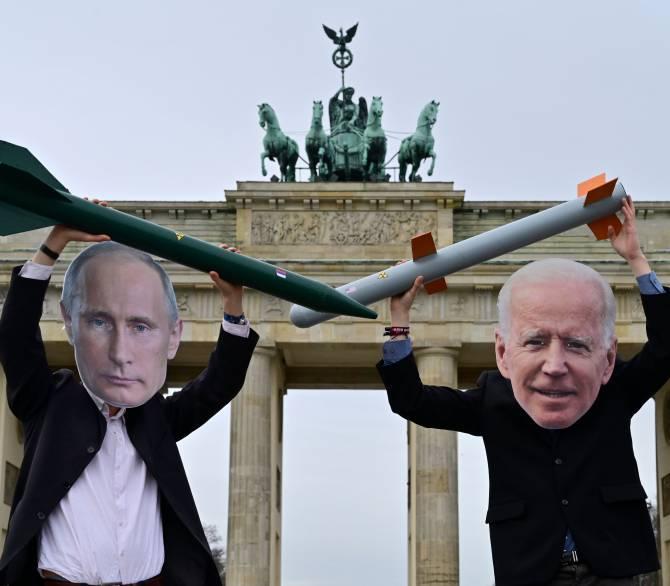 peace activists with Biden and Putin masks