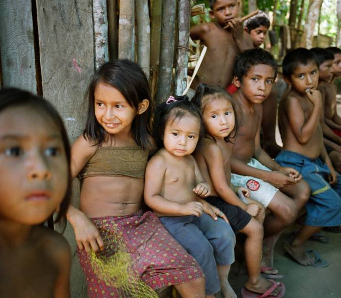 Children attend a birthday celebration at their village in a clearing in the rainforest. The Floresta Nacional do Tapajos (FLONA), a 6500 km2 protected reserve, was home to several small communities which lived on the banks of the Rio Tapajos river.; Getty