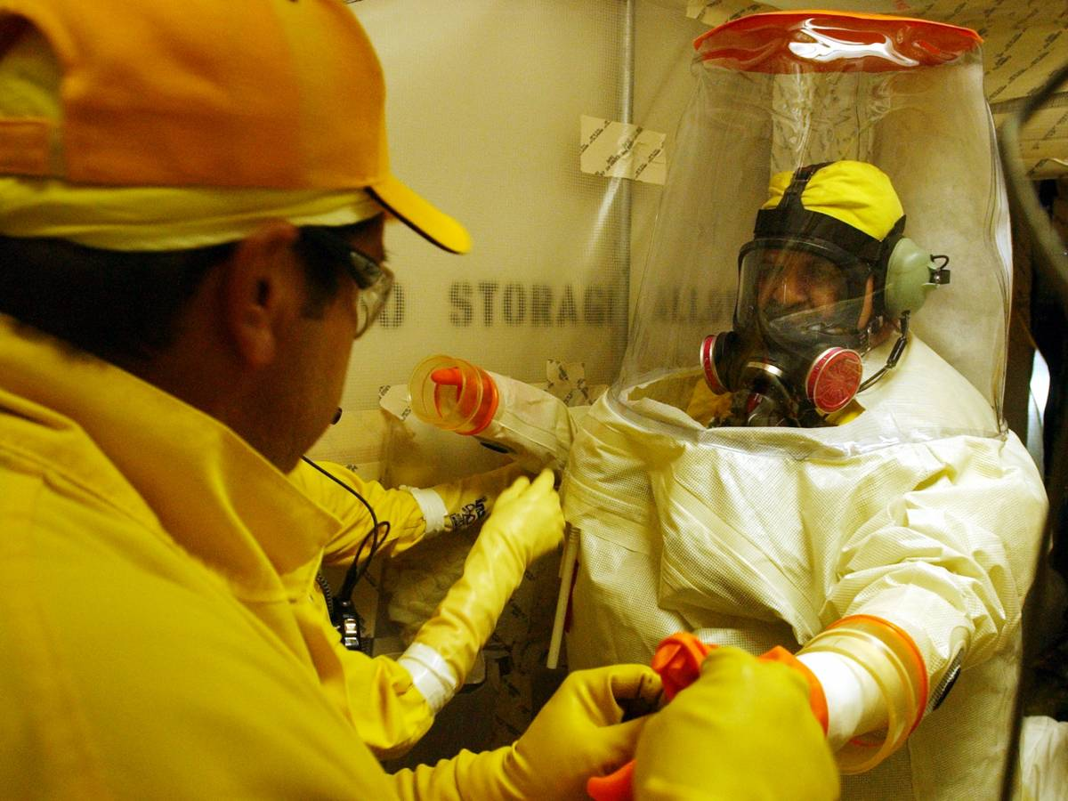 Rocky Flats workers help a skilled trades worker, put on his anti-contamination suit.