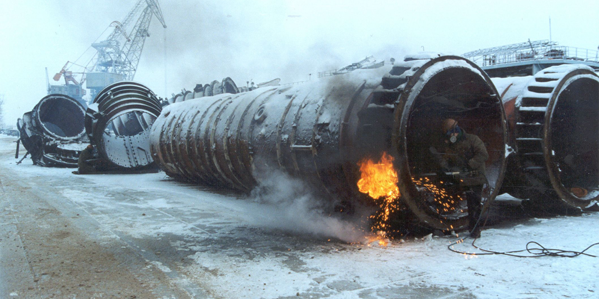 A man stands inside a ballistic missile tube, cutting into the shell with a metal torch. Other old tubes can be seen in the background of the scrapyard.
