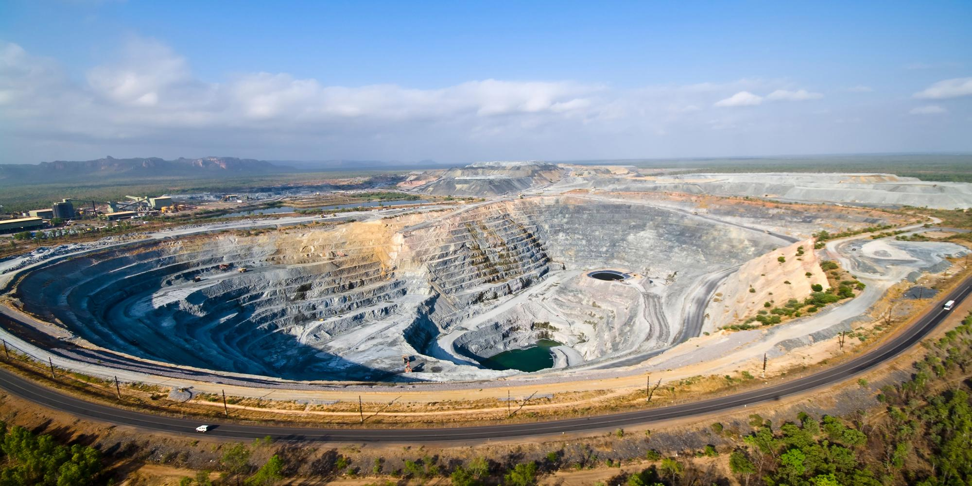 A large grey strip mine, with a stepped decline to the bottom, disrupts a green plains landscape.