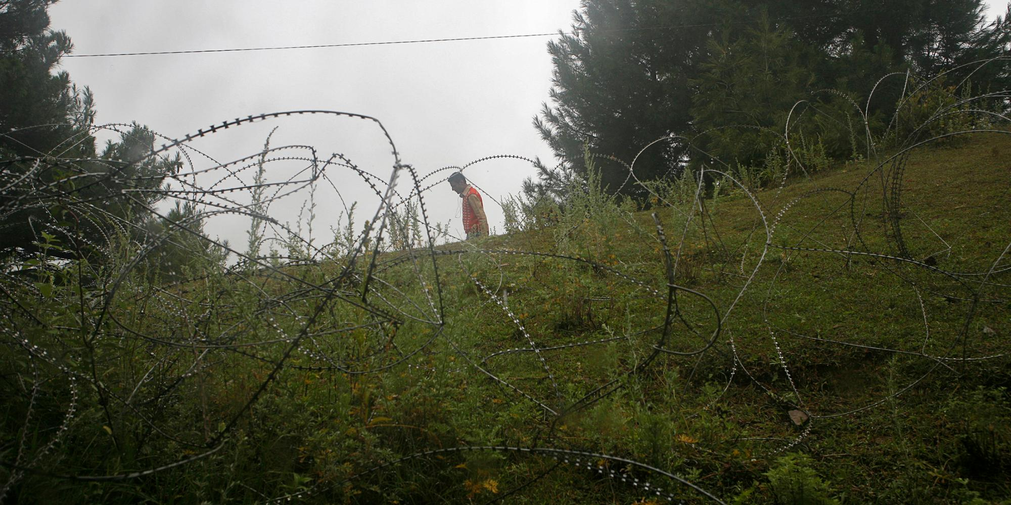 A man walks past abandoned razor wire.