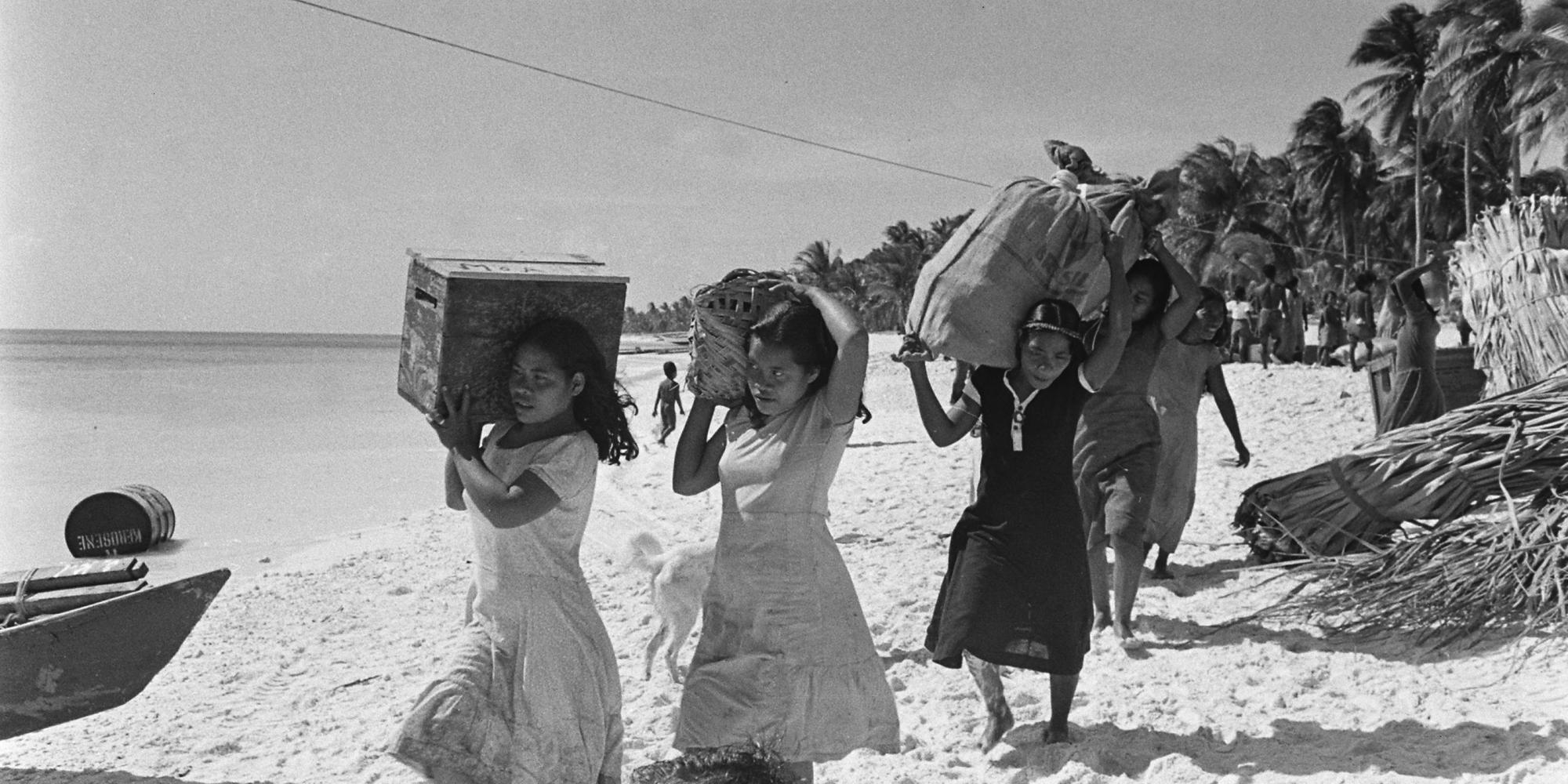 A group of women carry boxes and bags across a beach.