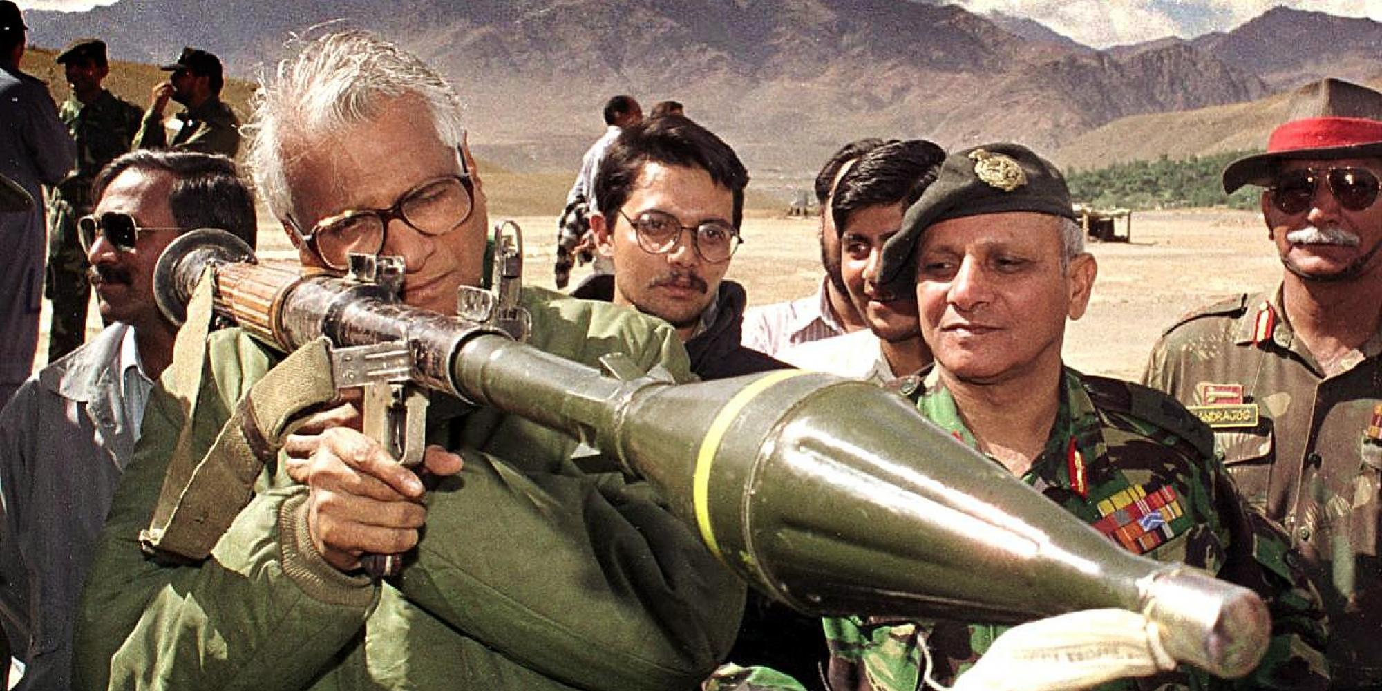 A man in thick-rim glasses stares down the sights of a rocket-propelled grenade. A crowd of men look on.