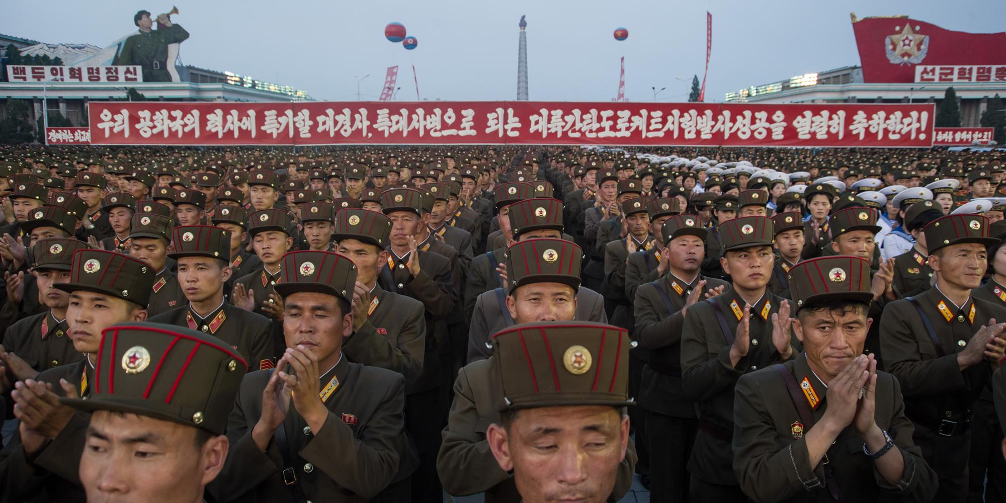 A sea of soldiers in brown uniforms stand in front of long red banner with white text.