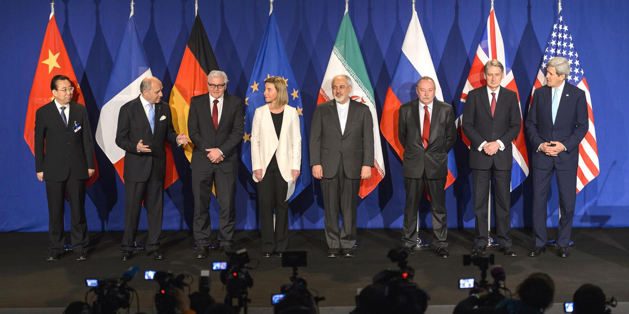 Officials in suits stand in front of their countries' respective flags, in front of a room of reporters.