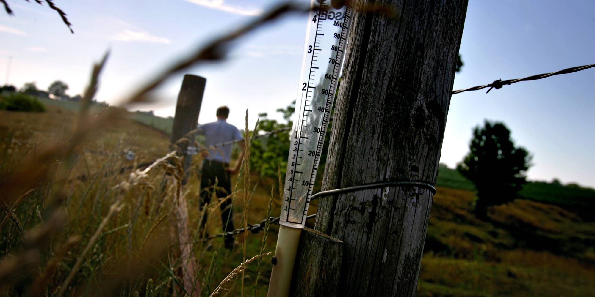 An empty rain gauge sits on a fence post on an Illinois farm.