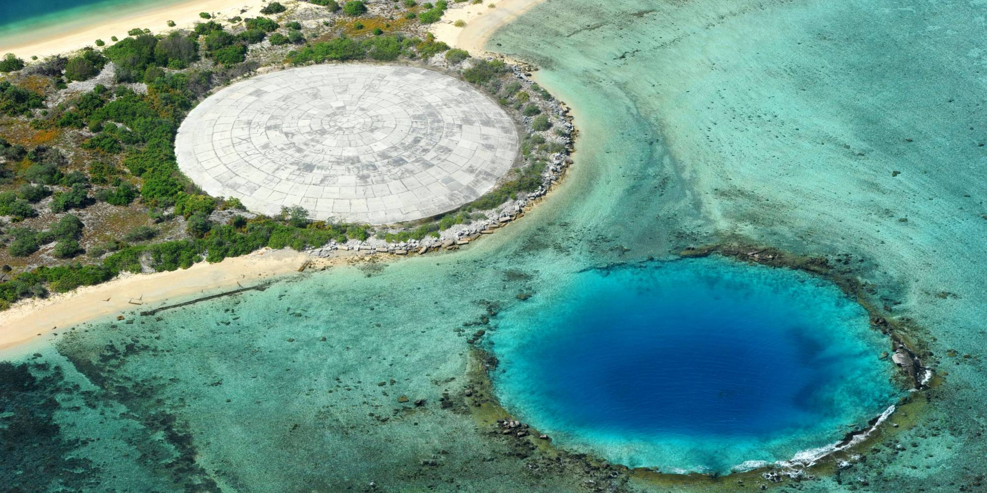 A crater covered by concrete to keep decontaminated soil (L) and another crater, both created by nuclear testingin Enewetak Atoll, Marshall Islands.