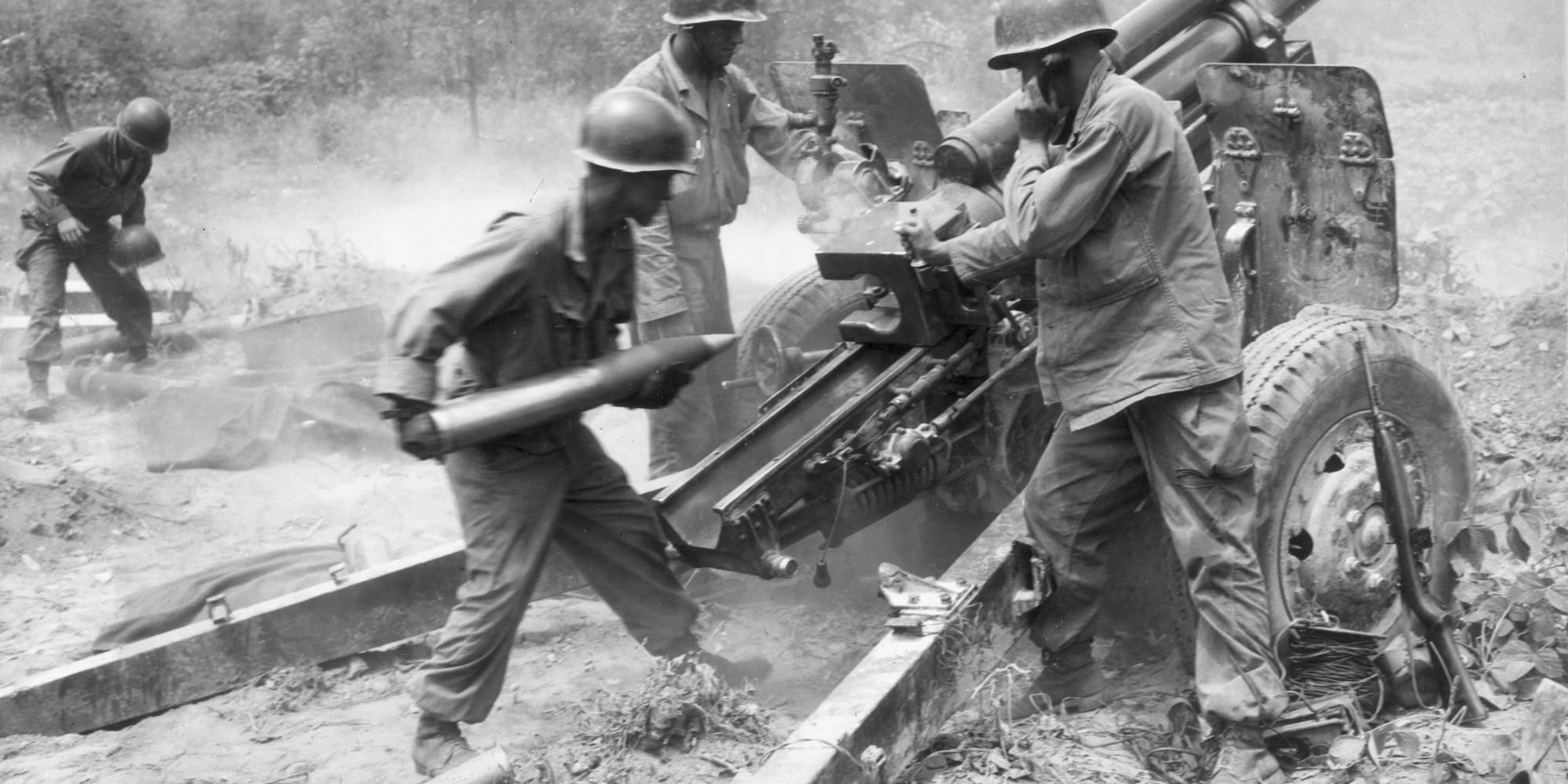 soldiers load howitzer gun