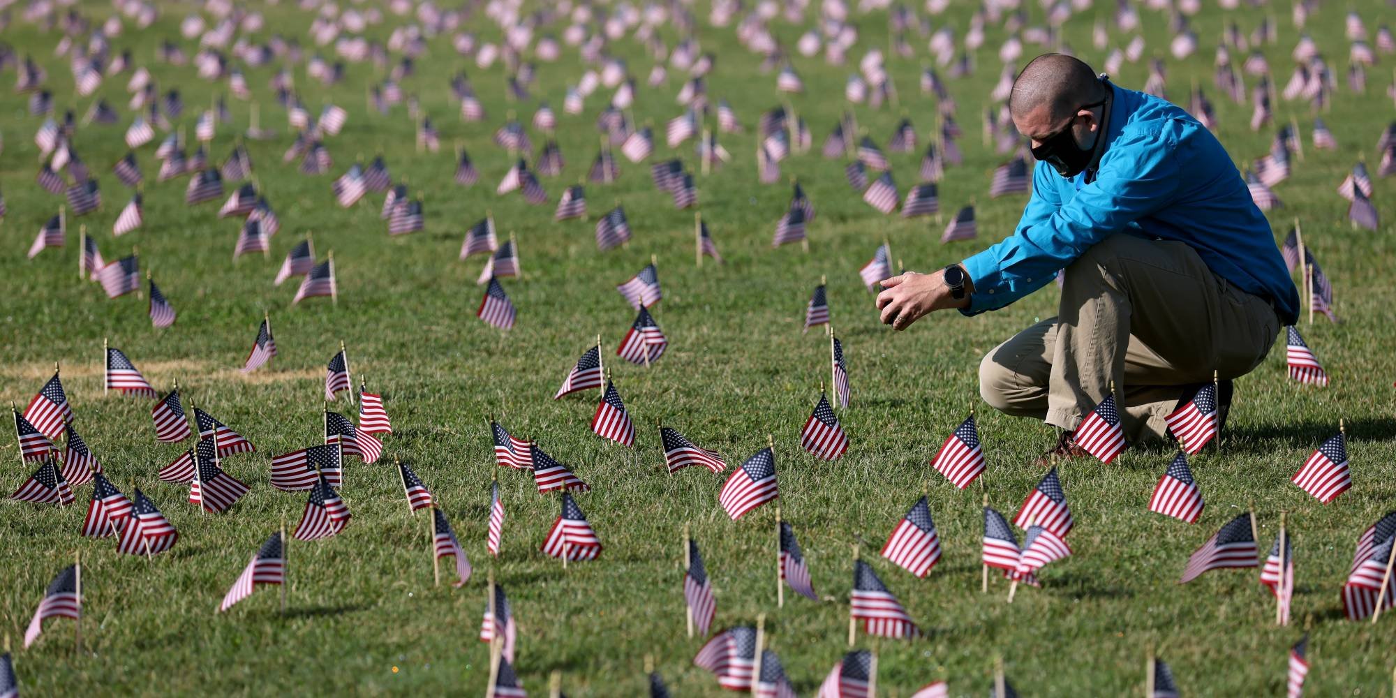man in field of small American flags
